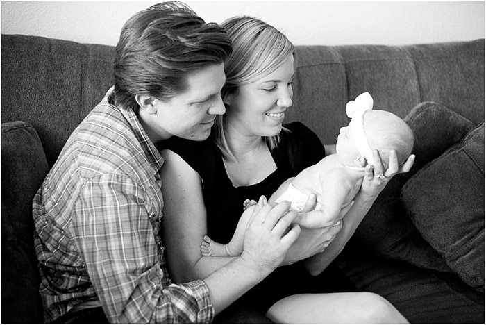A black and white lifestyle shot of a couple with their baby - newborn photography business tips
